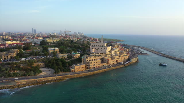 aerial shot of church in city by sea against sky during sunset, drone flying forward towards buildings - jaffa, israel - ジャファ点の映像素材/bロール