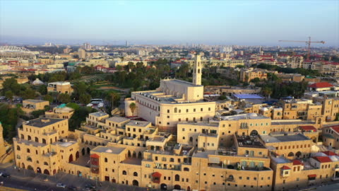 aerial shot of church with tourists in city against sky, drone flying forward over buildings during sunset - jaffa, israel - ジャファ点の映像素材/bロール