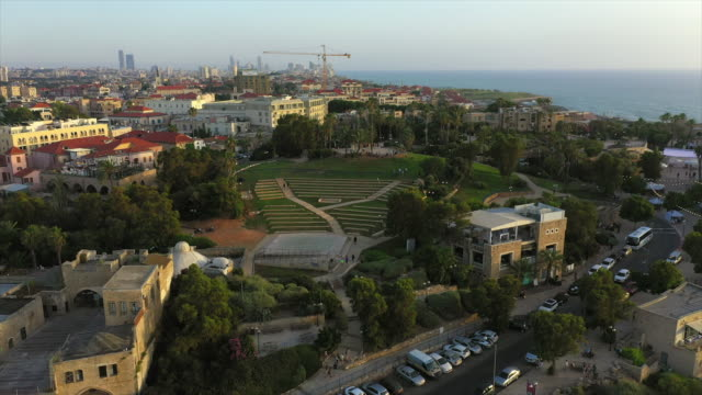 aerial shot of city by sea against sky during sunset, drone flying backward from tourists - jaffa, israel - jaffa stock videos & royalty-free footage