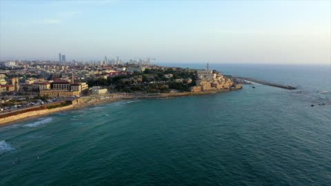 aerial shot of city by sea against sky during sunset, drone flying over waves near buildings - jaffa, israel - ジャファ点の映像素材/bロール