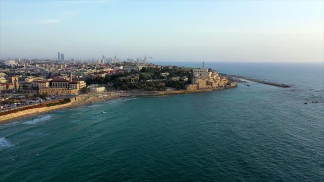aerial shot of city by sea against sky during sunset, drone flying over waves near buildings - jaffa, israel - jaffa stock videos & royalty-free footage