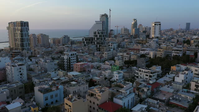 aerial shot of cityscape by sea against sky at sunset, drone descending forward over city - tel aviv, israel - テルアビブ点の映像素材/bロール