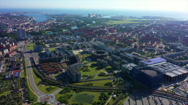 stockvideo's en b-roll-footage met aerial shot of cityscape by sea against sky on sunny day, drone flying forward over buildings in city - copenhagen, denmark - buitenwijk