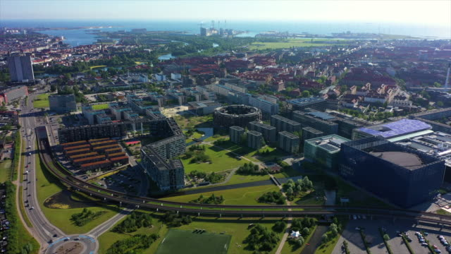 aerial shot of cityscape by sea against sky on sunny day, drone flying backward over buildings in city - copenhagen, denmark - copenhagen stock videos & royalty-free footage