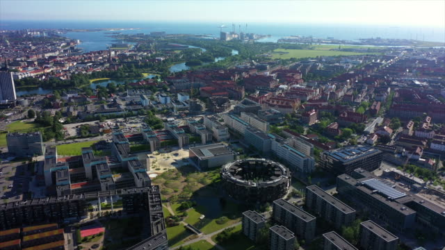 aerial shot of cityscape by sea on sunny day, drone flying forward over city against sky - copenhagen, denmark - denmark stock videos & royalty-free footage