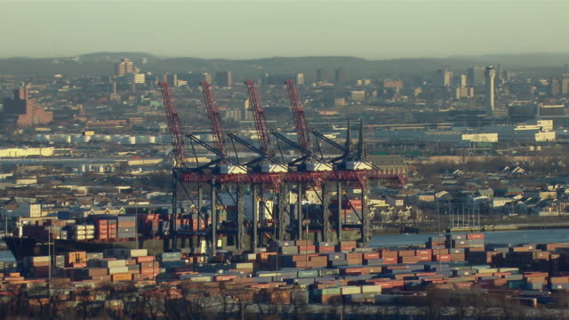 vídeos de stock e filmes b-roll de aerial shot of container cranes and stacks of shipping containers at the port newark elizabeth marine terminal in new jersey. - nova jersey