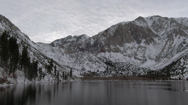 aerial shot of convict lake against snowcapped mountain range, drone flying backward over white landscape during winter - mammoth lakes, california - mammoth lakes video stock e b–roll
