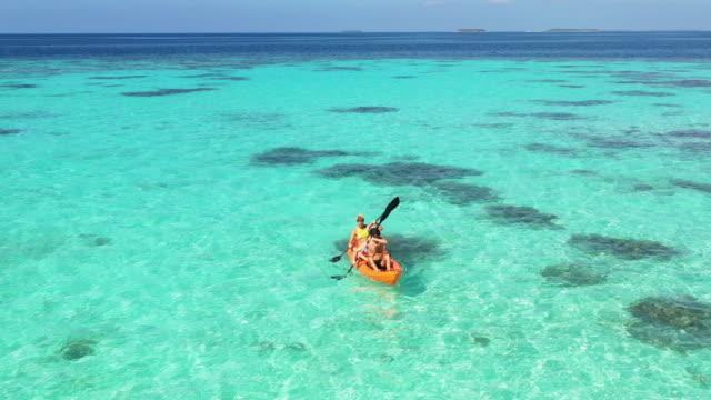 aerial shot of couple kayaking on tropical ocean - reef stock videos & royalty-free footage