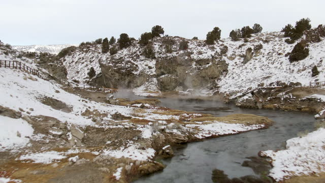 aerial shot of creek emitting steam amidst snow during winter, drone flying forward over hot creek geological site against sky - mammoth lakes, california - mammoth lakes video stock e b–roll