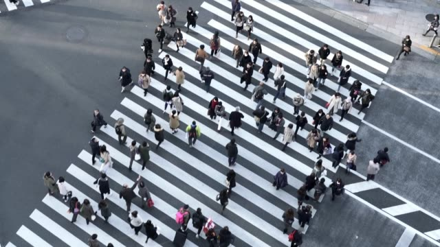 aerial shot of crowd crossing massive black and white crosswalk - pedestrian crossing stock videos & royalty-free footage