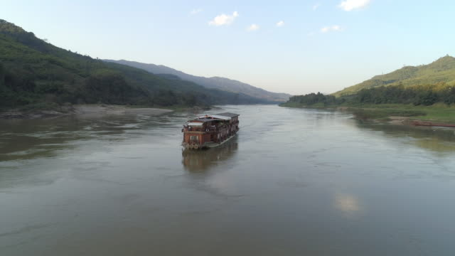 vídeos de stock e filmes b-roll de aerial shot of cruise ship moving on river amidst mountains against sky, drone flying over reflection in water against sky - mekong river, laos - cruzeiro