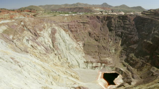 aerial shot of dirty pond at abandoned mine by city on sunny day, drone flying forward over open-pit quarry against mountains - bisbee, arizona - imperfection stock videos & royalty-free footage