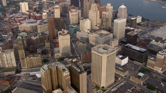 aerial shot of downtown detroit, tilting down over highrise buildings. - detroit michigan stock videos & royalty-free footage