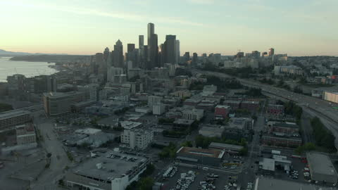 aerial shot of dr jose p rizal bridge in city by elliott bay, drone flying forward over modern cityscape against sky at sunset - seattle, washington - elliott bay stock videos & royalty-free footage