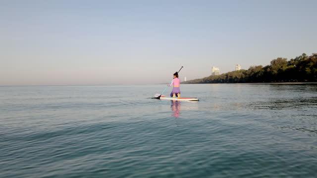 vidéos et rushes de projectile aérien de drone, corps extérieur extérieur d'étirement de plage d'exercice le matin. pratique de yoga du matin sur paddleboard avec la lumière du soleil douce sur la mer. - littoral
