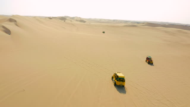 aerial shot of dune buggies moving on sand near city in desert, drone panning and moving along safari vehicles against sky - huacachina, peru - isoliert stock-videos und b-roll-filmmaterial