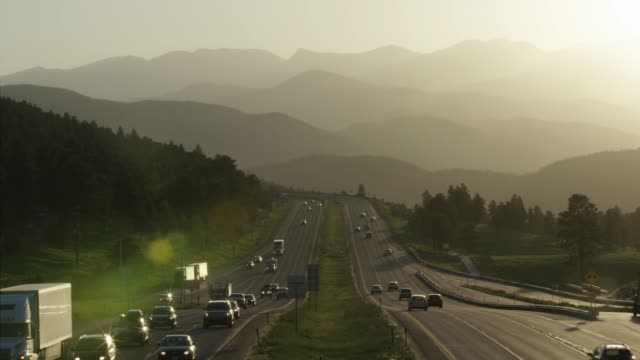 aerial shot of east and westbound highway traffic along interstate-70 in the rocky mountains of colorado at sunset - mountain range stock videos & royalty-free footage