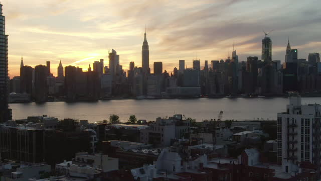 aerial shot of east river by manhattan against sky, drone flying backward from buildings in city at sunset - new york city, new york - international landmark stock videos & royalty-free footage