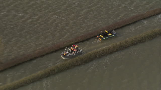 aerial shot of emergency services rescue boats amongst widespread flooding on the somerset levels - somerset levels stock videos and b-roll footage