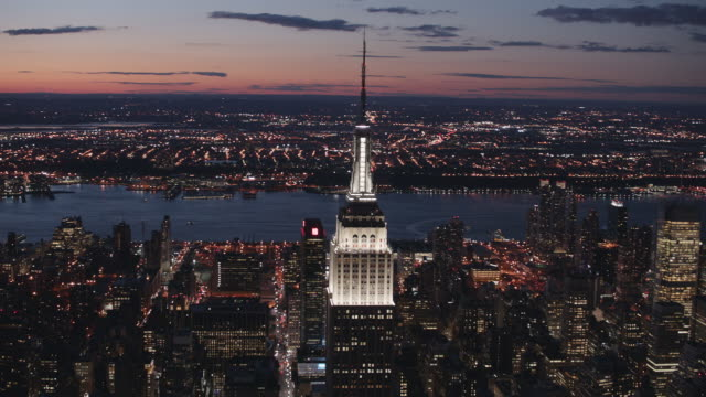 Aerial shot of Empire state building at night with lights on