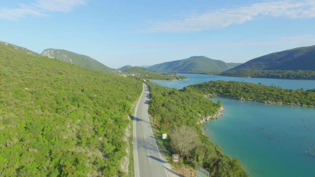 aerial shot of empty road on mountain by sea against sky, drone is descending - ston, croatia - good posture stock videos & royalty-free footage