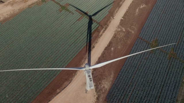 aerial shot of energy producing wind turbines on top of a hill - turbine stock videos & royalty-free footage