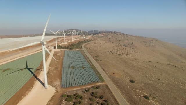 vídeos de stock, filmes e b-roll de aerial shot of energy producing wind turbines on top of a hill - israel