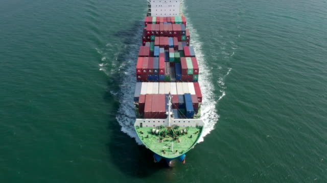 aerial shot of export container ship in ocean - cargo ship stock videos & royalty-free footage