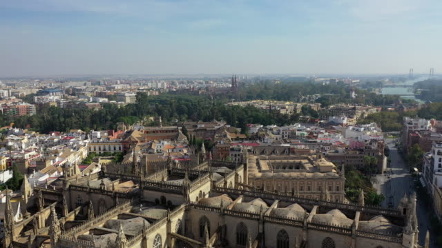 aerial shot of famous cathedral by tourists in city on sunny day, drone flying over religious building against sky - seville, spain - sunny video stock e b–roll