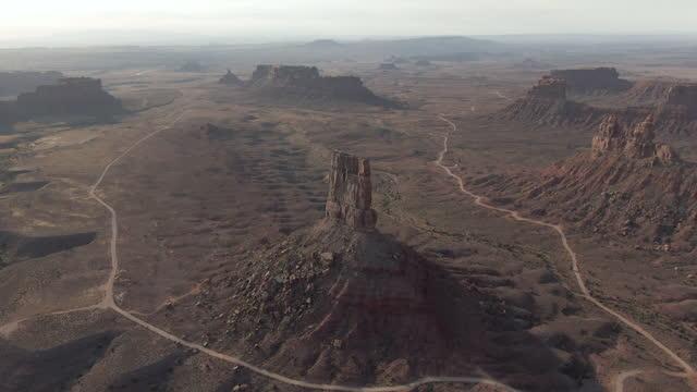 aerial shot of famous eagle plume tower in desert, drone flying backward from popular natural landmark against sky - valley of the gods, utah - natural landmark stock videos & royalty-free footage