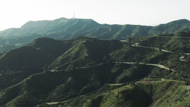 aerial shot of famous hollywood sign on mountain against sky, drone flying forward towards historical landmark on sunny day - los angeles, california - city of los angeles stock videos & royalty-free footage