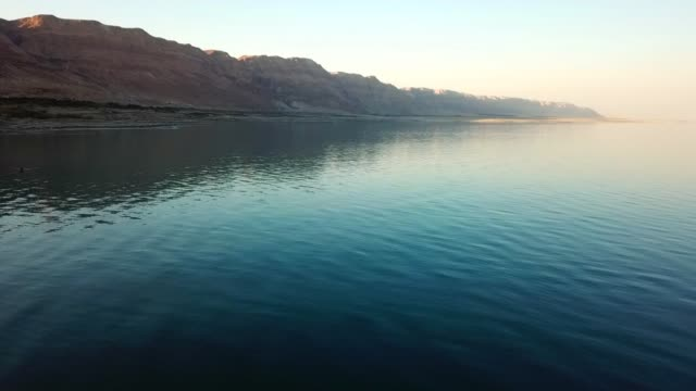 vidéos et rushes de aerial shot of famous salt lake near mountains against sky, drone flying backward over natural landmark - dead sea, israel - natural landmark