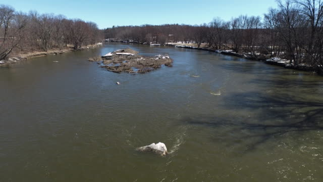 Aerial shot of fast moving river in country during winter