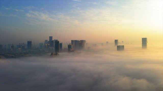 aerial shot of fog covering buildings in city, drone flying forward towards residential buildings against cloudy sky - tel aviv-yafo, israel - covering stock videos & royalty-free footage