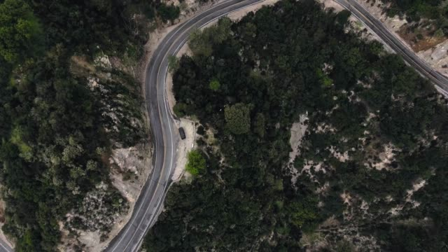 aerial shot of forest in mountains, winding road and black car (santa anita canyon, california, usa) - black canyon stock videos & royalty-free footage