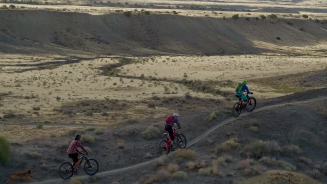 Aerial Shot of Four Mountain Bikers Riding Along a Curved Ridge on 18 Road in Fruita, Colorado