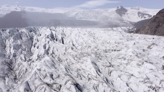 aerial shot of glacier and mountains against sky on sunny day, drone flying backward over winter landscape - southwestern iceland, iceland - wide angle stock videos & royalty-free footage