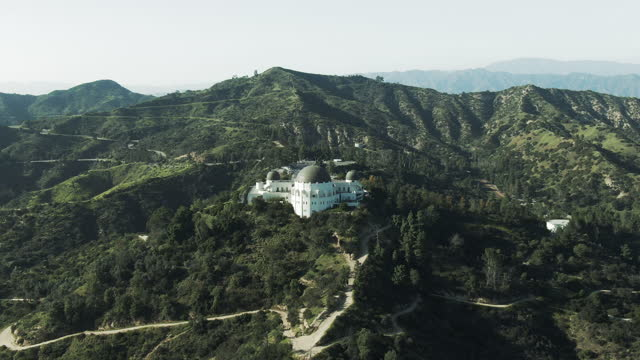 aerial shot of griffith observatory amidst plants and trees, drone flying backward from famous landmark on mountain against sky - los angeles, california - griffith observatory stock videos & royalty-free footage