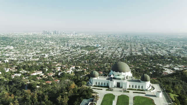 aerial shot of griffith observatory on mountain against sky, drone flying forward over cityscape on sunny day - los angeles, california - griffith observatory stock videos & royalty-free footage