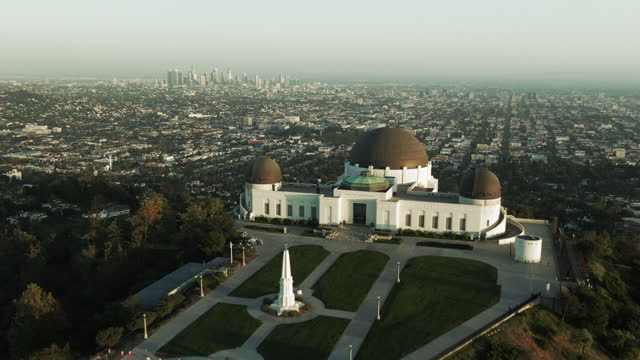 aerial shot of griffith observatory on mountain by cityscape, drone flying forward towards city against sky at sunset - los angeles, california - griffith observatory stock videos & royalty-free footage