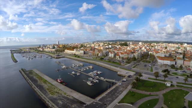 stockvideo's en b-roll-footage met aerial shot of harbor in city against sky, drone is flying backwards - figueira da foz, portugal - achterstevoren