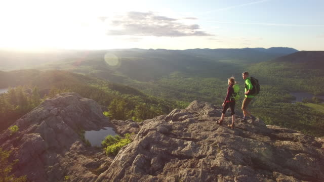 vidéos et rushes de aerial shot of hiker atop mountain ridgeline. - maine