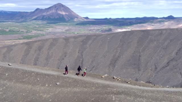 vídeos y material grabado en eventos de stock de disparo aéreo de excursionistas a lo largo del cráter del volcán en islandia - paisaje espectacular