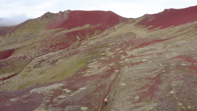 aerial shot of hikers walking on mountain trail against sky, drone descending over people hiking on rocky landscape - rainbow mountain, peru - volcanic crater stock videos & royalty-free footage