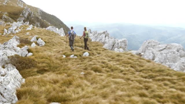 Luftaufnahme von Wandern paar walking im mountain ridge