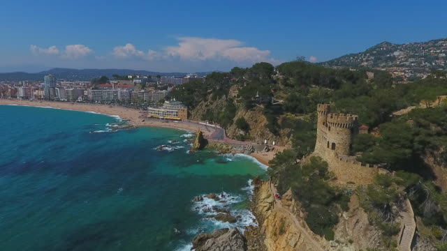 aerial shot of historic castle on cliff by sea near city against sky, drone flying over rock formation on sunny day - lloret de mar, spain - mar点の映像素材/bロール