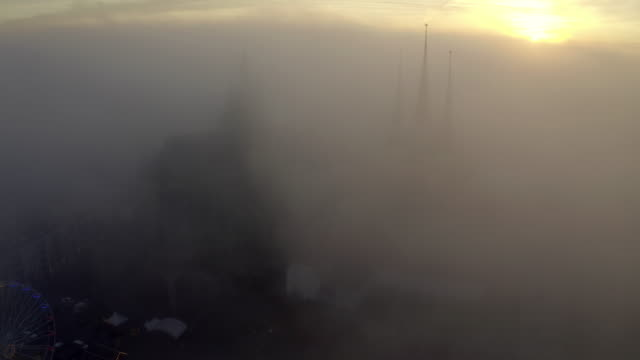 aerial shot of historic cathedral seen through fog in city, drone is flying backwards during sunset - erfurt, germany - fog stock videos & royalty-free footage