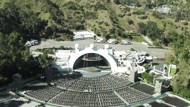 aerial shot of hollywood bowl amidst trees by highway, drone descending forward from famous amphitheater on sunny day - los angeles, california - famous place stock videos & royalty-free footage