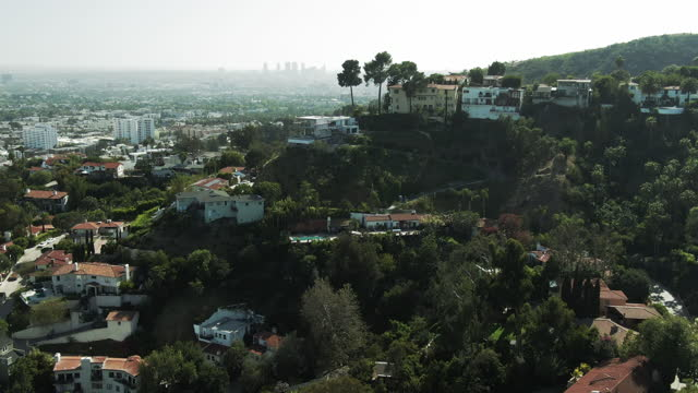 aerial shot of hollywood bowl amidst trees by houses on hill, drone flying forward from famous amphitheater in city on sunny day - los angeles, california - amphitheatre stock videos & royalty-free footage