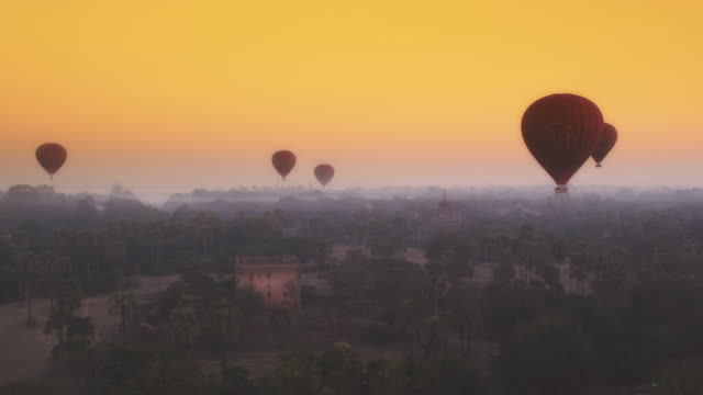 Aerial shot of hot air balloons floating over temples at sunrise in Myanmar